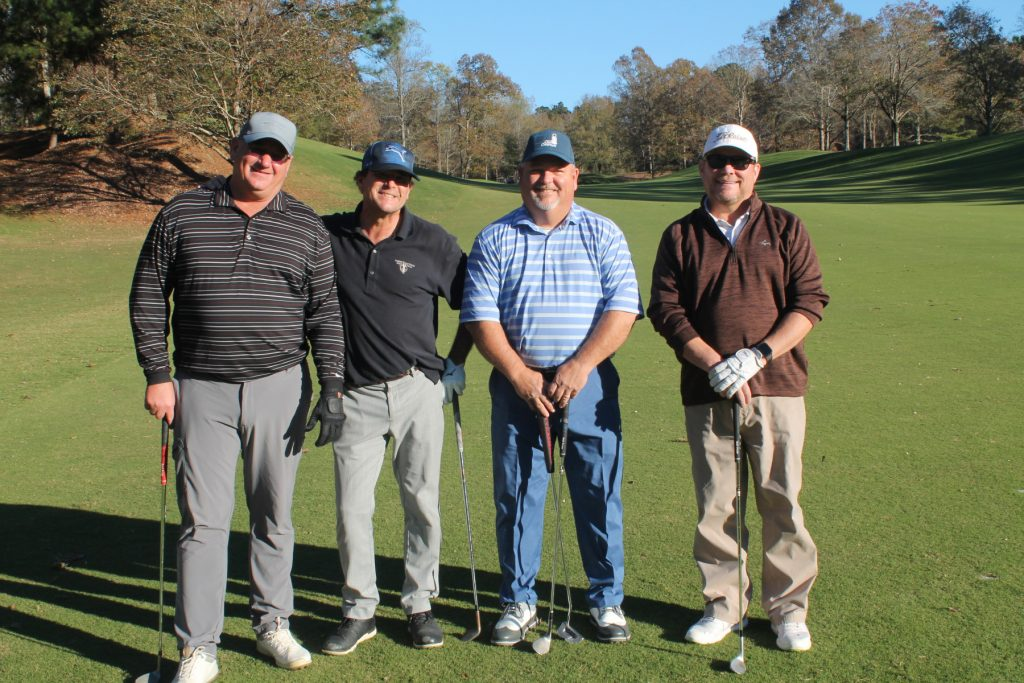 4 golfers pose for a picture