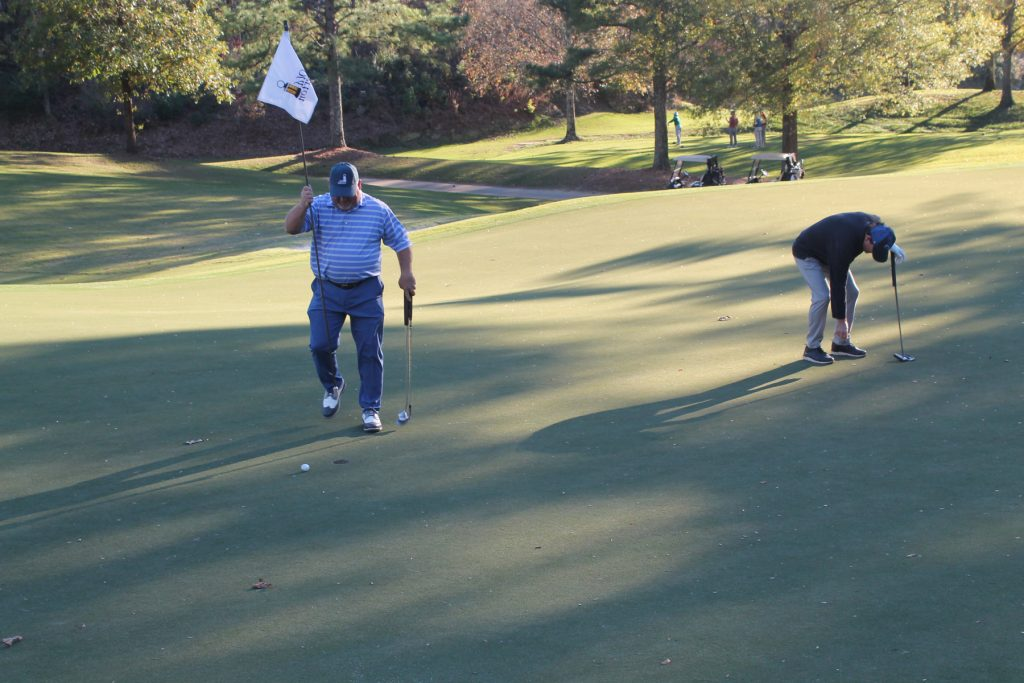 A golfer carries a flag while another positions his ball on the green
