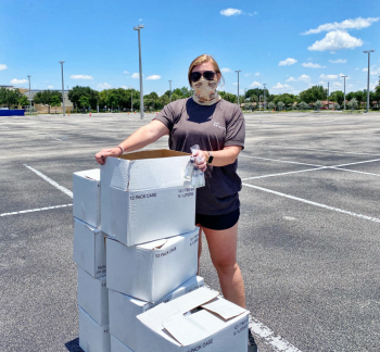 Woman stands in empty parking lot with boxes.
