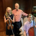 Dr. Heath Turner and children with instruments in a wood paneled room
