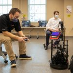 two students in a cream room use a remote control with a robot