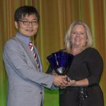 Dr. Yoon accepting an award in front of an iridescent yellow curtain