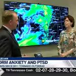 news screen capture of two people in a room with weather radar on tv