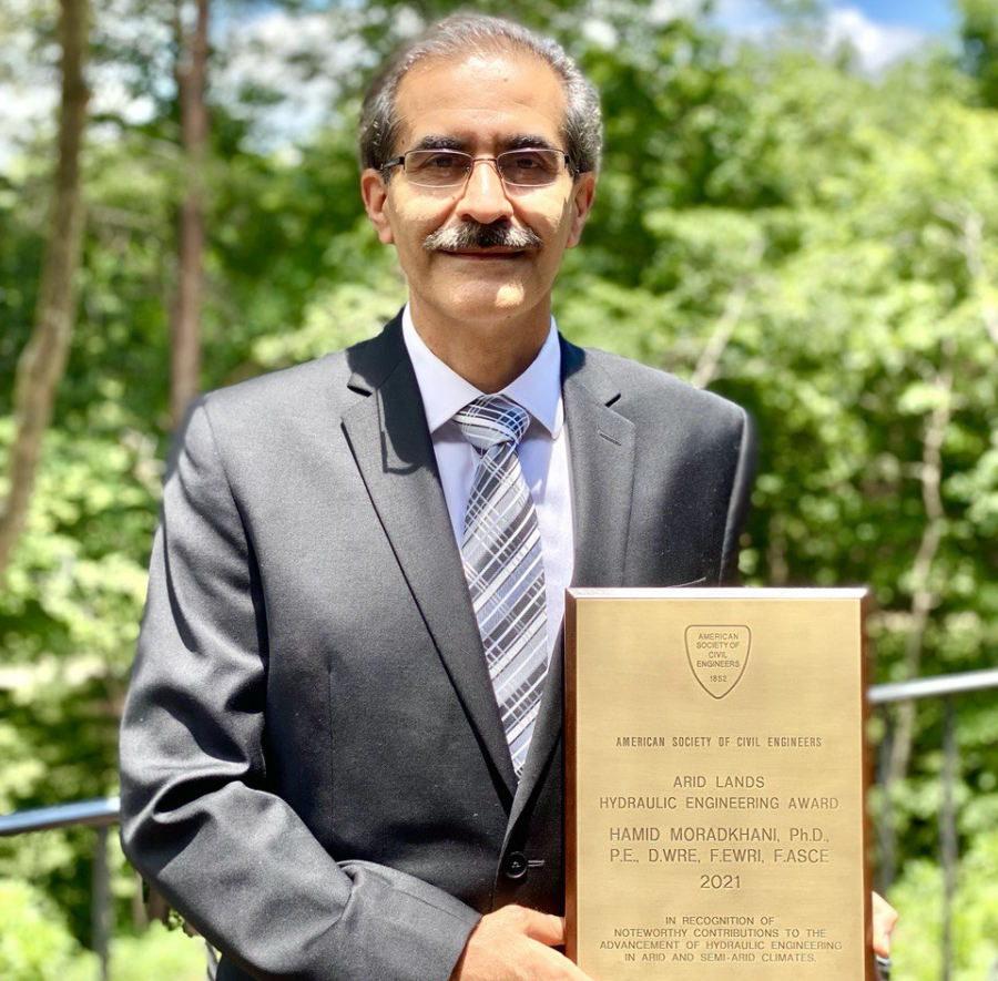Dr. Hamid Moradkhani holding his award outside on a sunny day