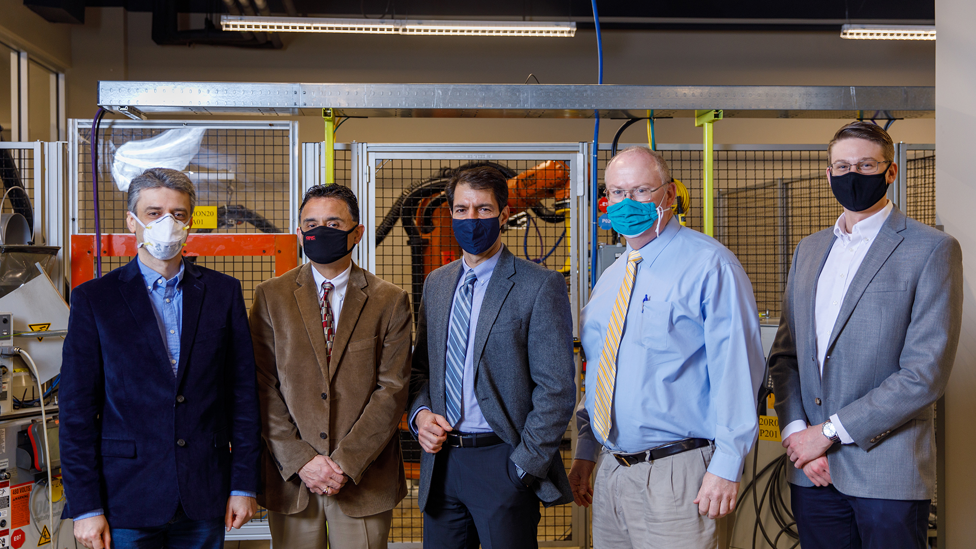 Lineup of faculty all wearing masks in the lab