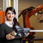 Roya Salehzadeh holds a control with a caged wielding machine in background