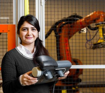 Roya Salehzadeh holds a controller next to a heavy welding machine