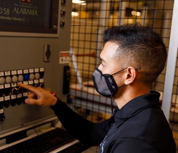 student pressing a button on a machine