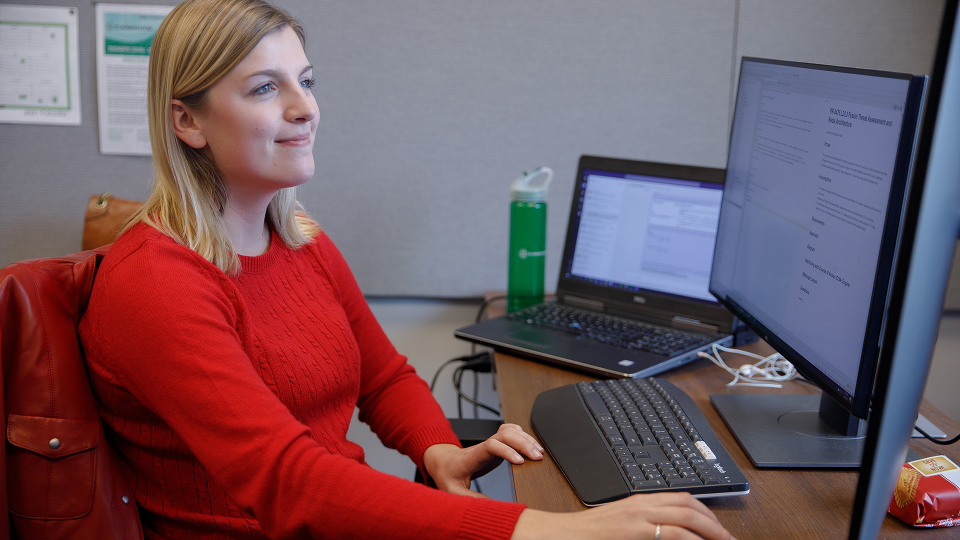 A female student in red works on a computer and 3 screens