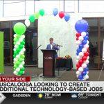 news screen capture of a man at a podium under a balloon arch