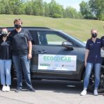 5 people stand outside next to their ecocar