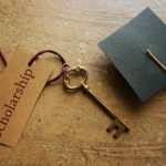 a key with the tag 'scholarship' tied to it and a paper graduation cap