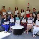 Faculty and staff stand in room holding certificates